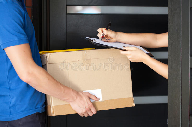 Woman signing parcel delivery papers. Delivery guy holding package while woman is signing documents royalty free stock photo