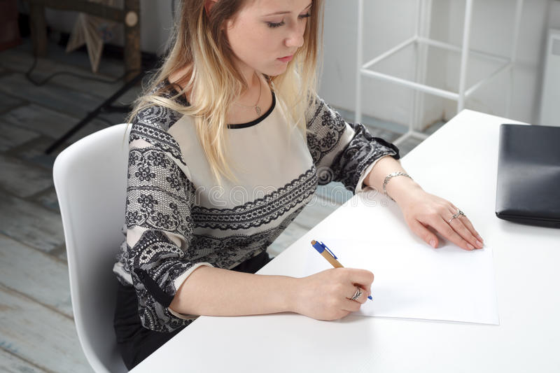 Woman signs documents on white background. stock photo