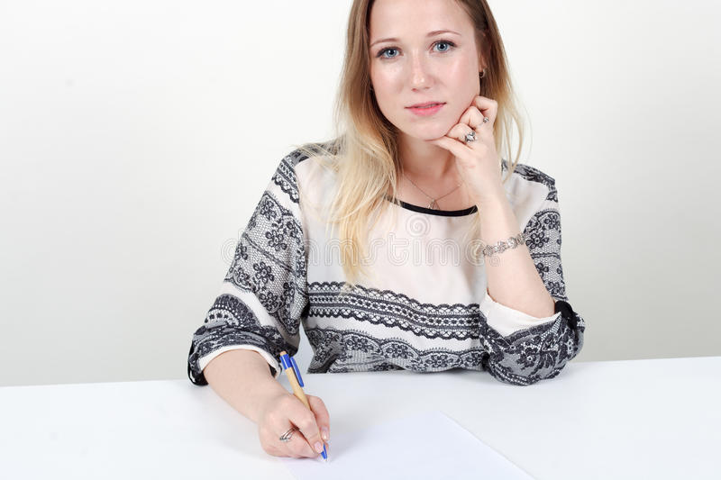 Woman signs documents on white background. stock photography