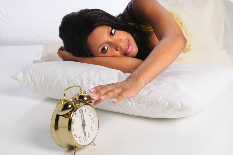 Woman Silencing Alarm Clock stock images