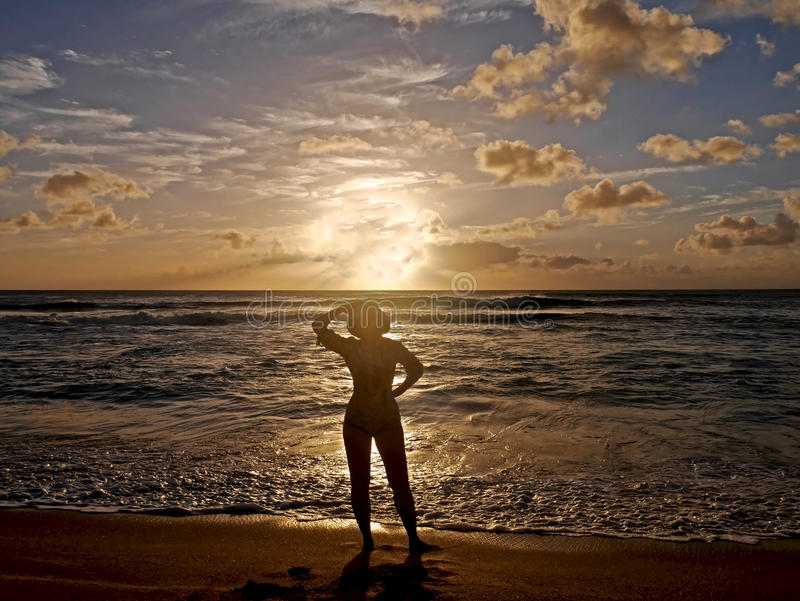 Woman silhouette against ocean at sunset. stock images