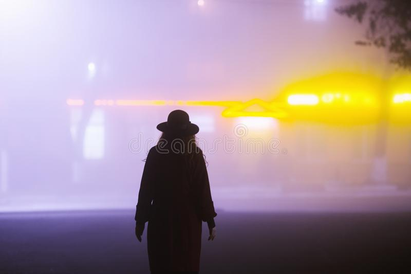 Woman silhouette on background of the night city in fog. Thick mist in dark scary evening city. Dark noir silhouette in hat on royalty free stock images