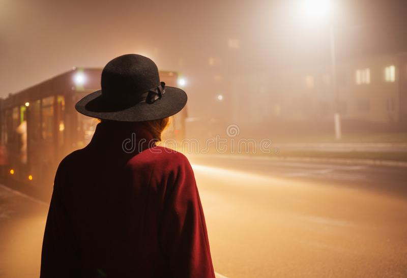 Woman silhouette on background of the night city in fog. Thick mist in dark scary evening city. Dark noir silhouette in hat on. Background of fog. Alone woman royalty free stock photo