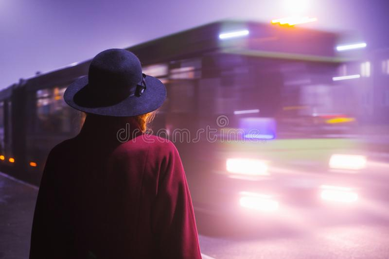 Woman silhouette on background of the night city in fog. Thick mist in dark scary evening city. Dark noir silhouette in hat on. Background of fog. Alone woman royalty free stock image