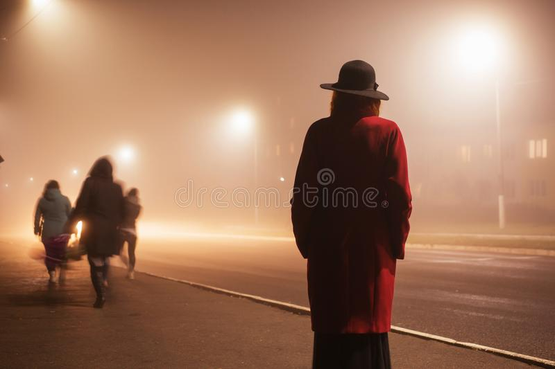 Woman silhouette on background of the night city in fog. Thick mist in dark scary evening city. Dark noir silhouette in hat on. Background of fog. Alone woman royalty free stock images