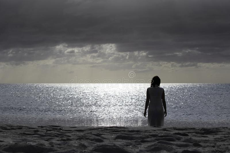 Woman silhouette from behind dressed in a light white dress walks sadly and thoughtfully towards the dark sea at dawn with. Dramatic sky stock photos