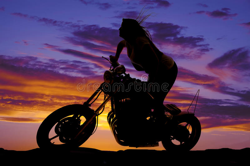 Woman silhouette bike stand lean forward stock photo