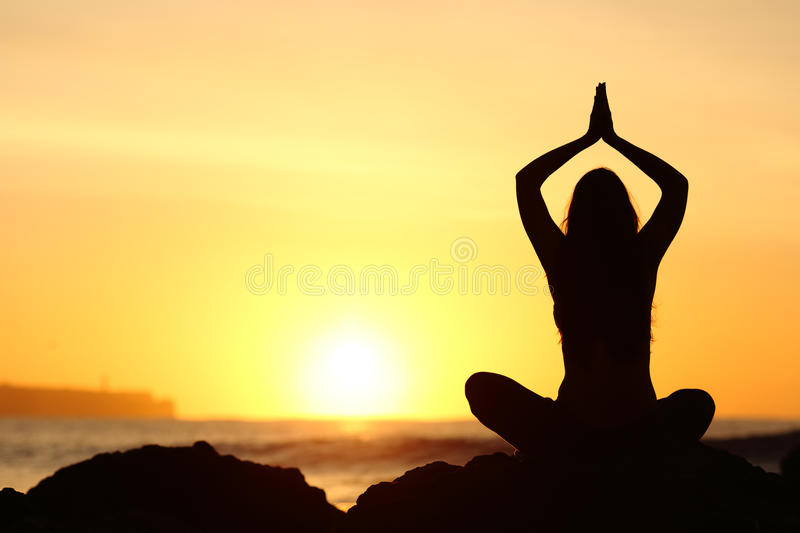 Woman silhouette doing yoga exercises royalty free stock image