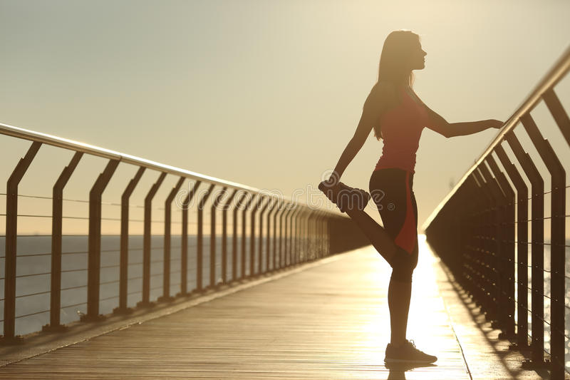 Woman silhouette exercising stretching on a bridge stock photo
