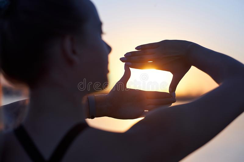 Woman silhouette framing sun with fingers at sunset. Hand shape of a camera across the sky royalty free stock photography