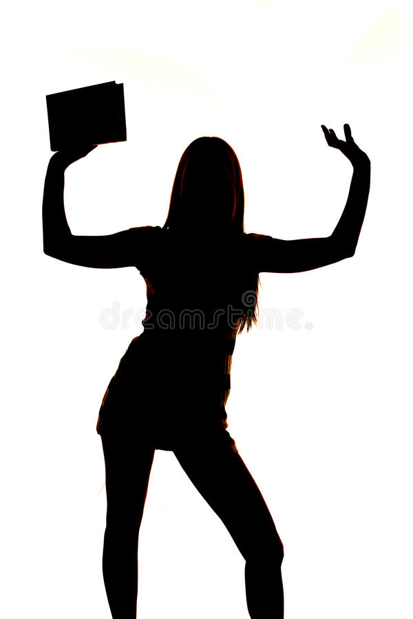 Woman silhouette holding up one book stock image
