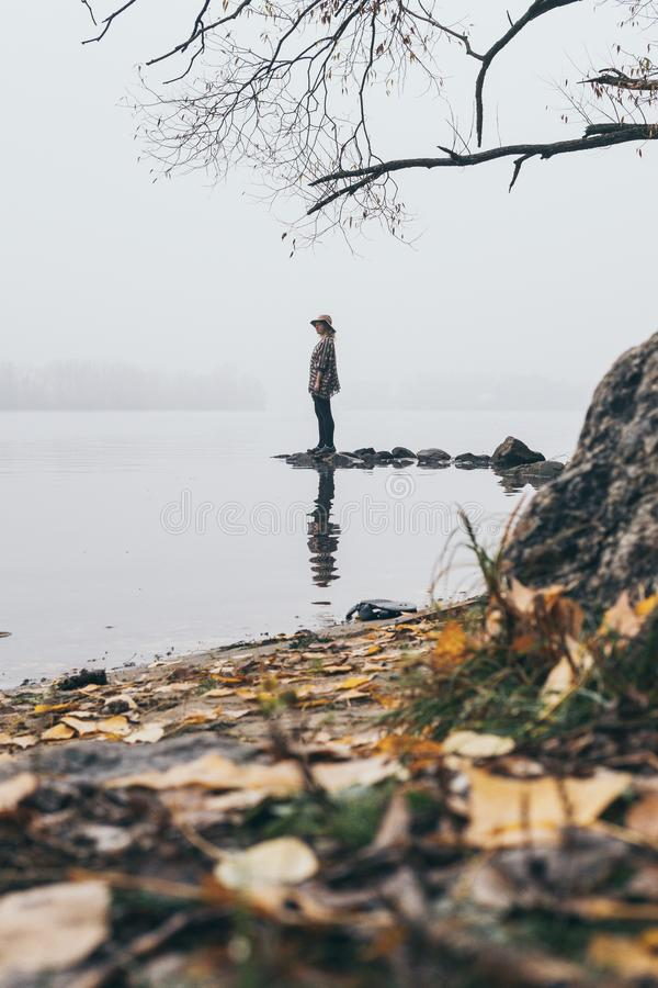 Woman silhouette on the river bank in the morning fog. Woman silhouette standing on the river bank in the morning fog. Vertical orientation, girl, mist stock images