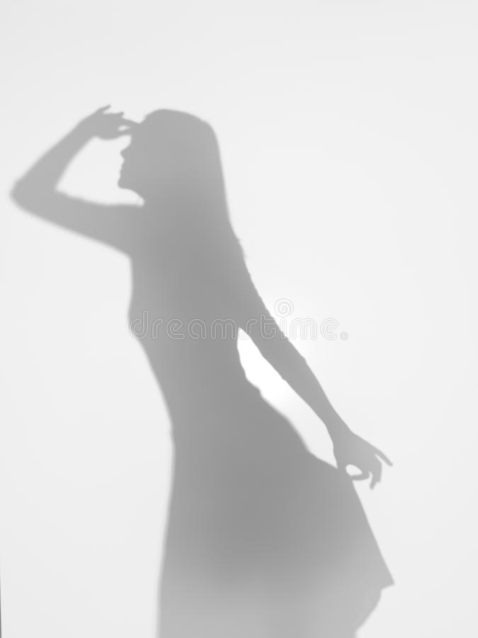 Woman silhouette seeking for something far away. Female body silhouette gazing far away and holding her dress elegantly with one hand, behind a diffuse surface stock photo