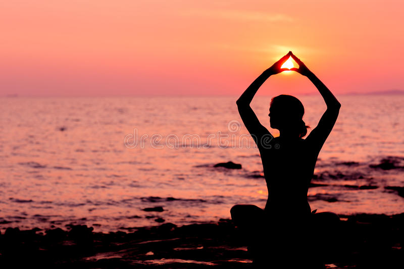 Woman silhouette sitting in lotus position on sea background back lit. Woman silhouette sitting in lotus position on sunset sea background, back lit royalty free stock images