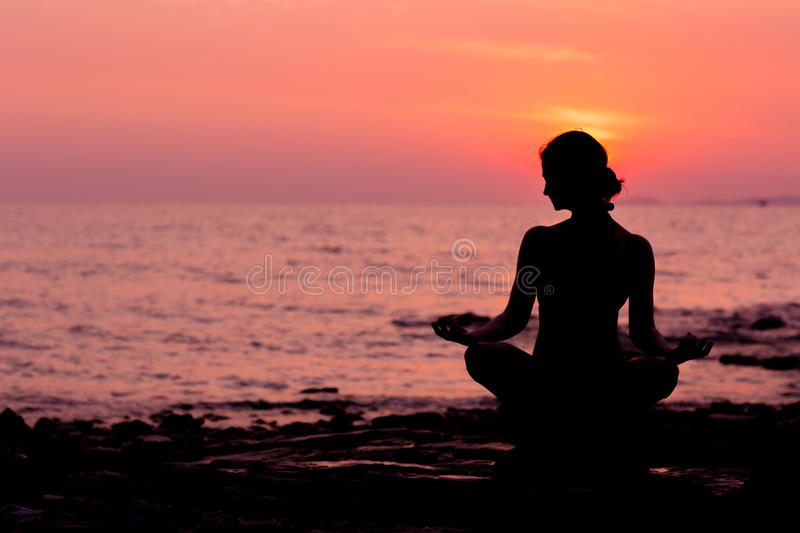 Woman silhouette sitting in lotus position on sea background back lit stock images