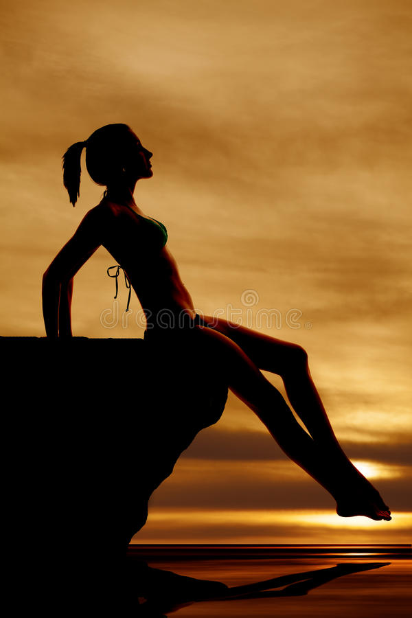 Woman silhouette sitting on rock by water. A silhouette of a woman sitting on a rock by the water royalty free stock photos