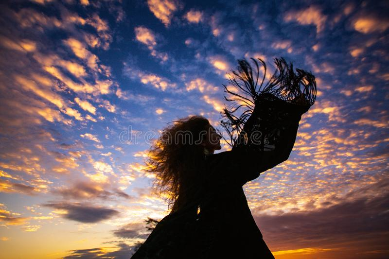 Woman silhouette sunset sky sleeves flight fringe. Woman silhouette sunset sky sleeves flight stock images