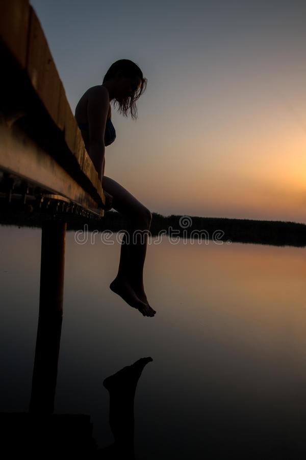 Woman silhouette in sunset on the wooden dock. royalty free stock images