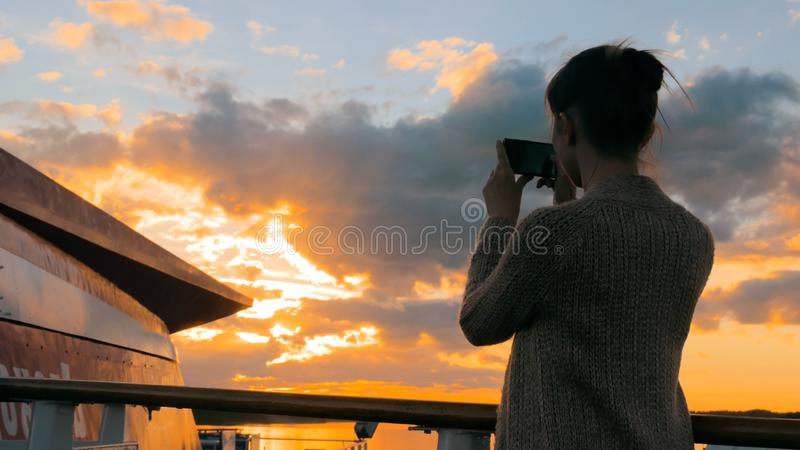 Woman silhouette taking photo of sunset with smartphone on deck of cruise ship. Woman silhouette taking photo of beautiful sunset with smartphone on deck of stock photography