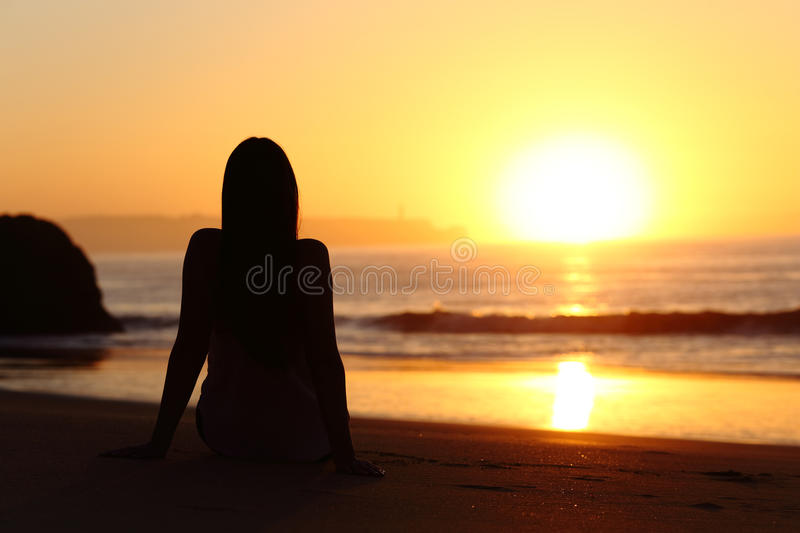 Woman silhouette watching sun at sunset stock photography