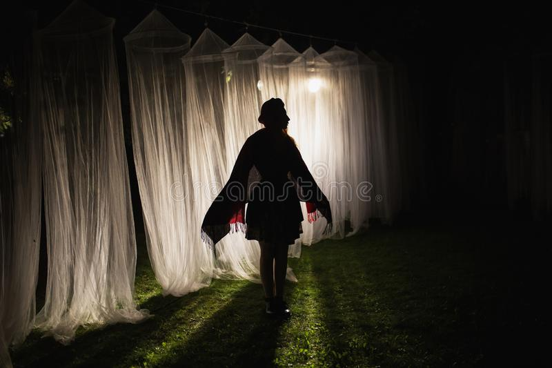 Woman silhouette. White long canopies are illuminated by the light of the lantern on a dark night. Conceptual photography. Mysterious silhouette on a dark royalty free stock images