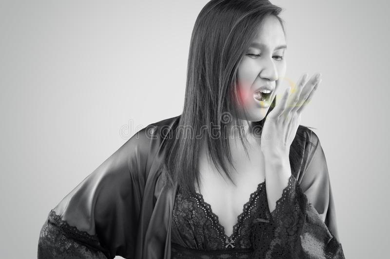 Bad breath. The woman in silk nightgown and lace robe checking her breath with hand on a gray background, Halitosis concept of a woman with bad breath, Bad royalty free stock photography