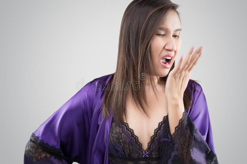 Halitosis. The woman in silk nightgown and purple robe checking her breath with hand on a gray background, Halitosis concept of a woman with bad breath, Bad stock photo