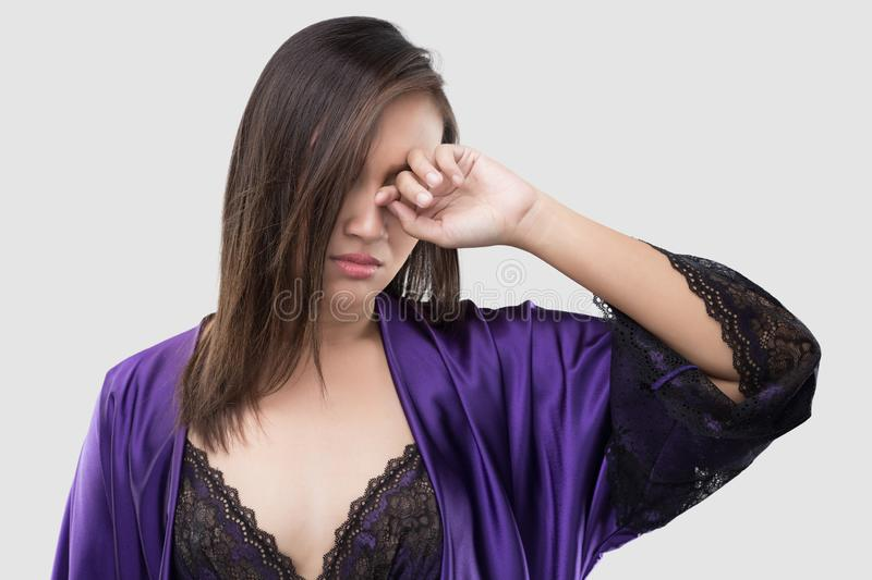 Have itching in the eye. The woman in silk purple nightgown and lace robe rubs her eye with a finger against the gray background, Women in violet satin nightwear royalty free stock image