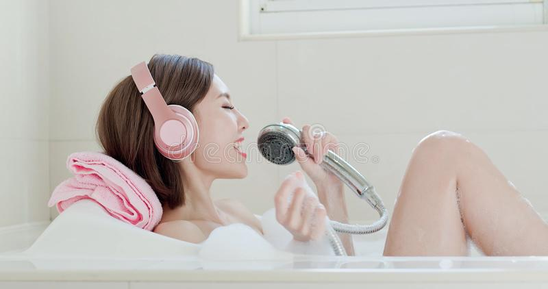 Woman sing song in bathtub. Beauty woman wear headphone and sing song in bathtub royalty free stock photo
