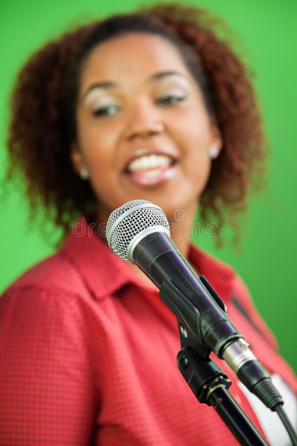 Woman Singing With Focus On Microphone stock photography