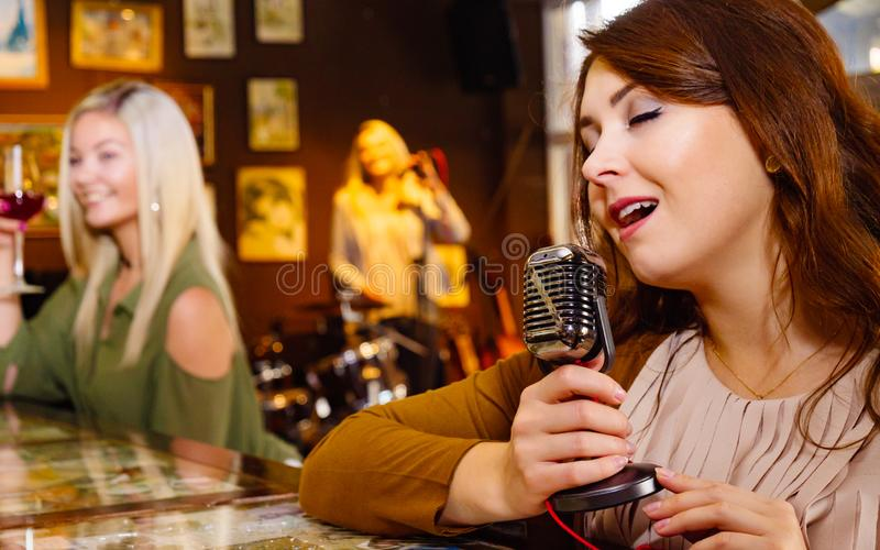 Woman singing with microphone stock images