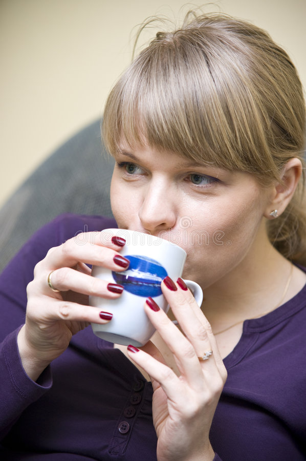 Woman sipping coffee. A portrait of a woman sipping coffee from a mug stock photography