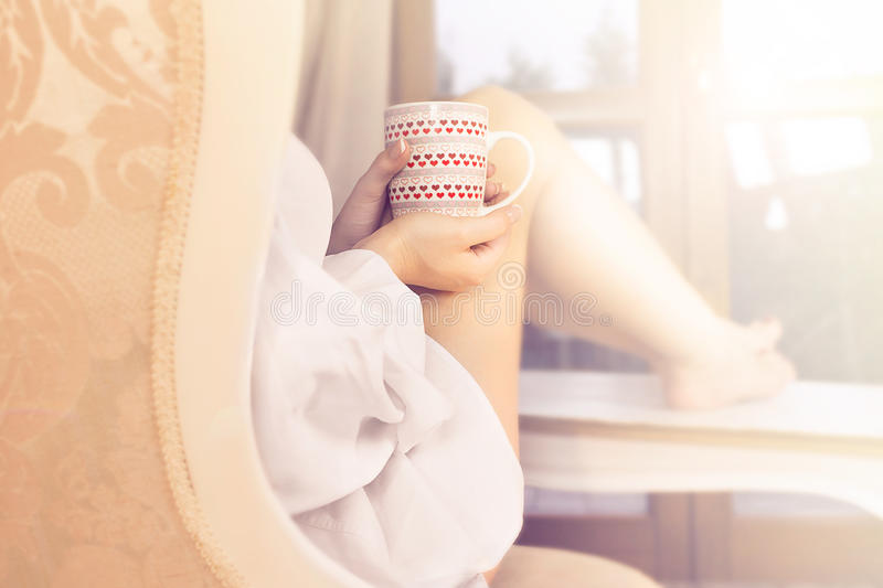 Woman sipping coffee in a magic moment of quiet. In her home stock photography