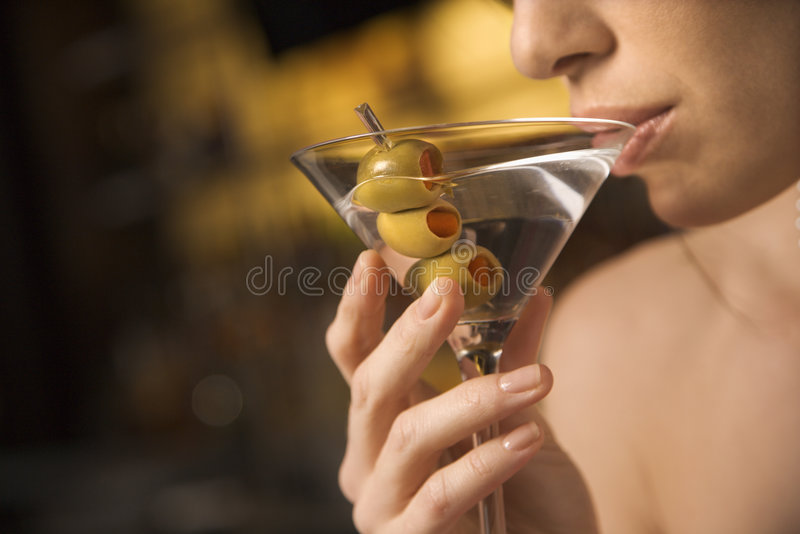Woman sipping martini. Close up of mid adult Caucasian woman drinking a martini with three olives royalty free stock photo