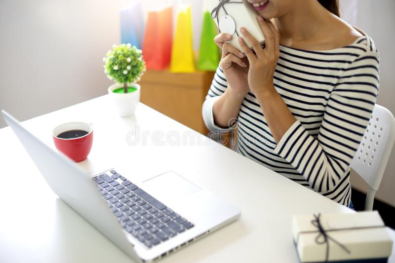 woman sit at computer table look at the product stock photography
