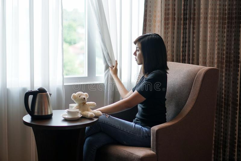 Woman sitting in hotel room look out the window royalty free stock images