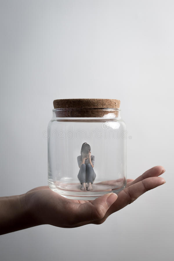 Woman sit in jar. The depression woman sit imprisoned in jar royalty free stock photo