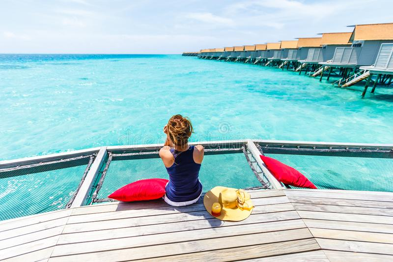Woman sit on net over sea. stock photography