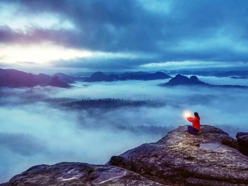 Woman sit on summit in hands holding flash bolb. Girl waiting stock image