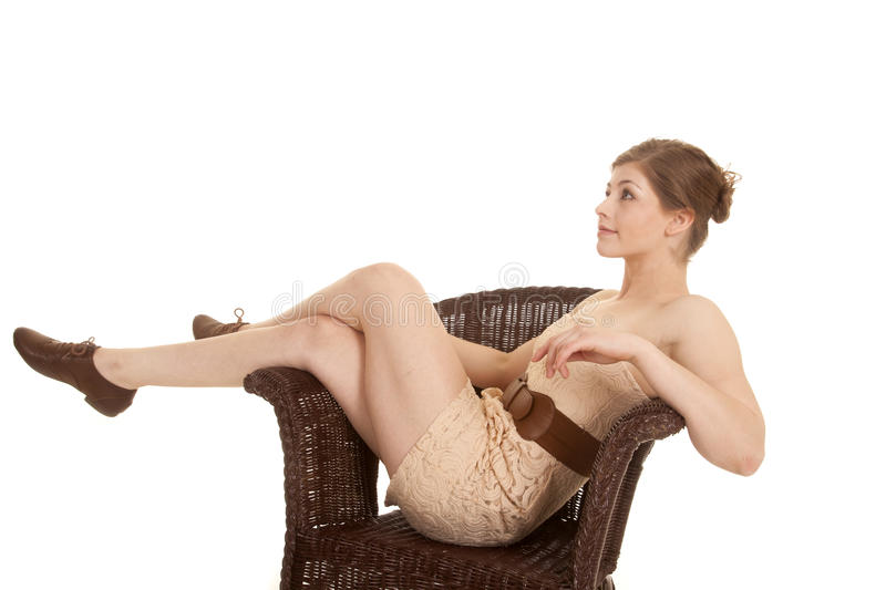 Woman sit in tan dress and belt legs on chair. A woman sitting in a chair looking up in her dress royalty free stock photos
