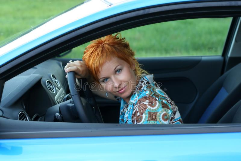 Woman is siting in a car stock photography