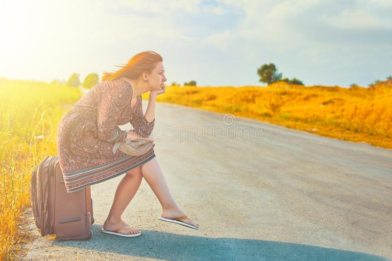Woman sits on baggage. Cute female person in summer dress and hat hitchhiking with suitcase on the road at fall. Woman sitting on baggage royalty free stock photography