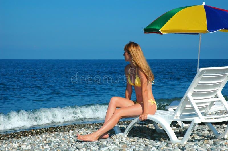 Woman sits at coast under umbrella stock photo