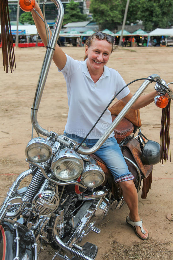 Woman sits on a cool bike. stock images