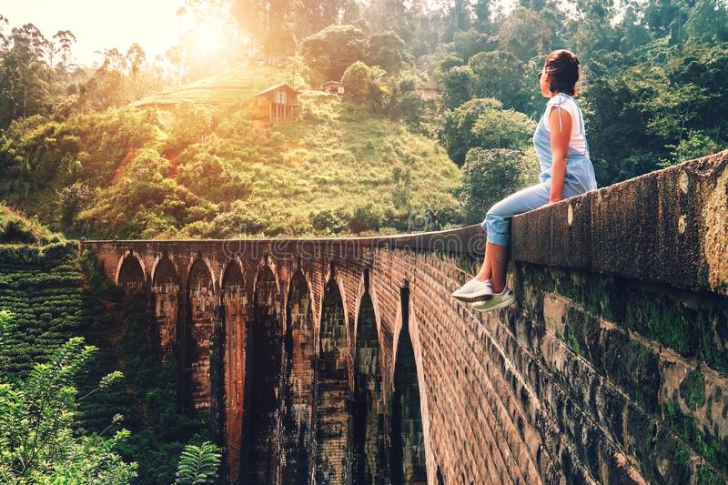 Woman sits on the Demodara nine arches bridge the most visited s. Ight of Ella town in Sri Lanka stock photo