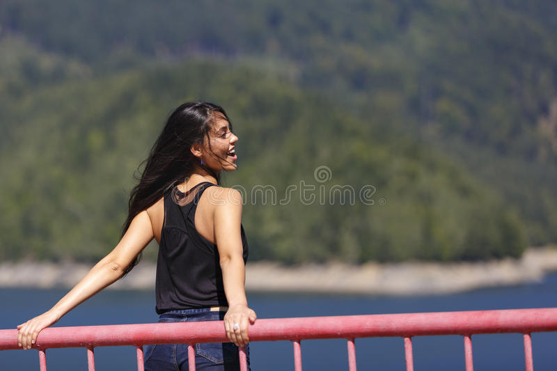 Woman sits on the edge of a dam stock images