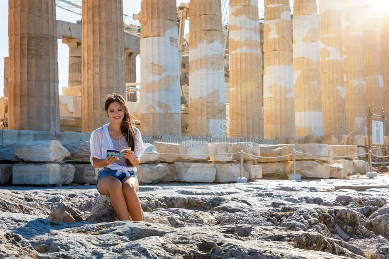 Woman sits in front of the columns of the Parthenon Temple at the Acropolis of Athens stock photo
