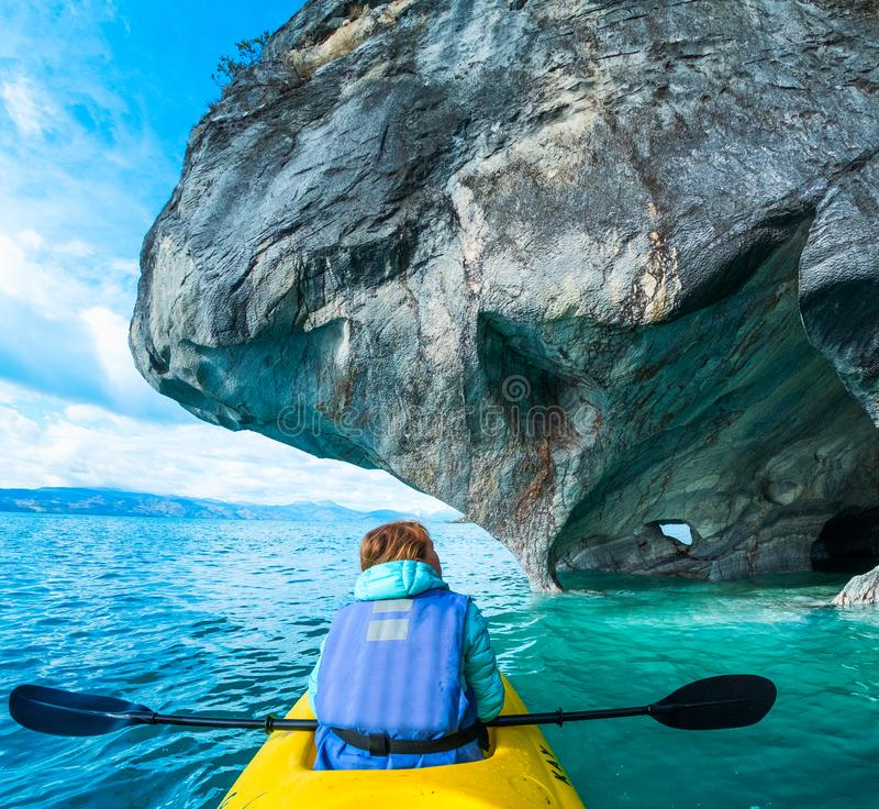 Woman paddles kayak. Woman sits in kayak and explores the Marble Caves and rocks on the lake of General Carrera, Chile stock photo