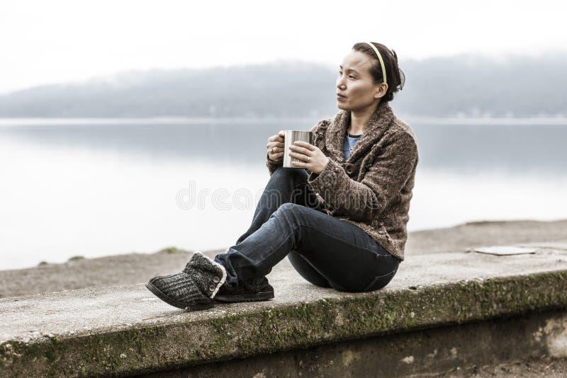 Woman sits on ledge by lake. royalty free stock photo