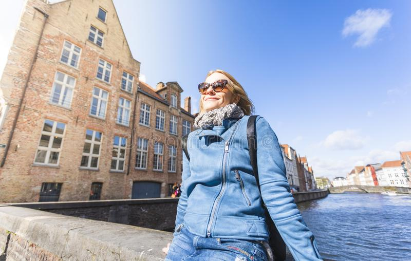 Woman sits near water on Jan van Eyck Square in Bruges, Belgium. A young female tourist sits near the water and basks in the sun on Jan van Eyck Square in Bruges stock photo